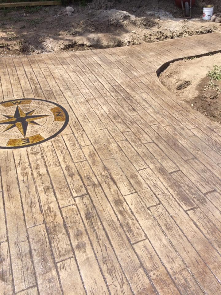 patio arriere avec motifd planche de bois et boussolle acid stain
